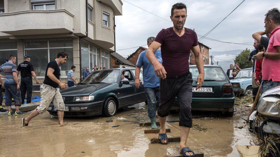 man walking across makeshift walkway of wooden plans through floodwater, 7 August 2016