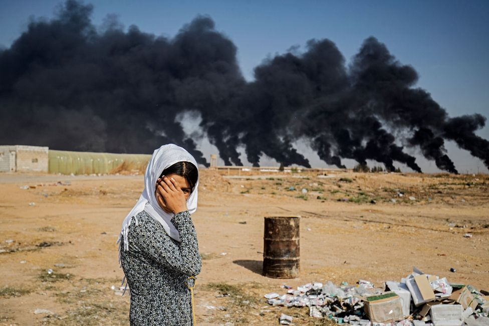 A woman covers her face against a background of smoke plumes