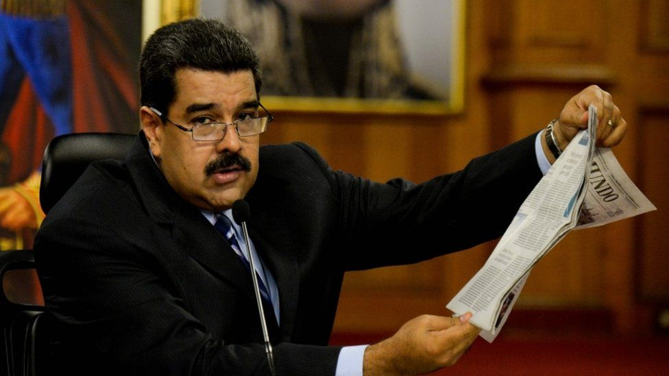 Nicolas Maduro holds a copy of a Spanish newspaper during press conference in Caracas