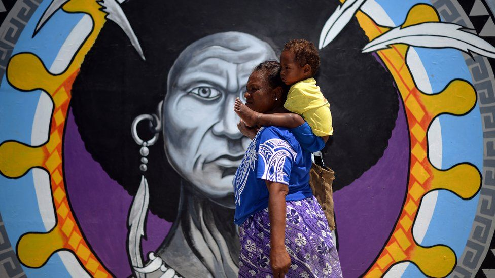 A Papuan woman walks in front of a mural in downtown Port Moresby on November 13, 2018, ahead of the Asia-Pacific Economic Cooperation (APEC) summit in Port