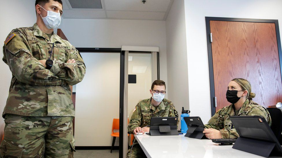 US national guard members are being trained for task in Tumwater, Washington - one person standing in a room and two sitting, all wearing masks