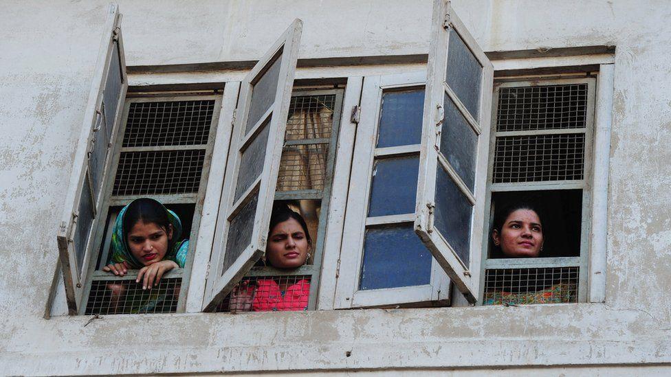 Pakistani women watch celebration from window of a building in Islamabad