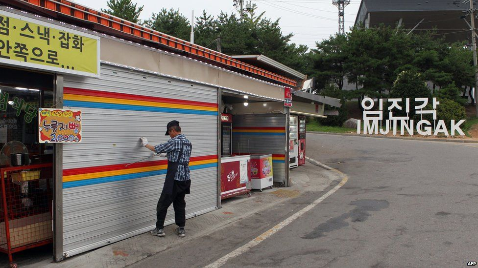 A South Korean man pulls down a shutter of his shop at the Imjingak Peace Park near the Demilitarized zone dividing the two Koreas in Paju on 20 August 2015, as residents of several border villages are ordered to evacuate their homes for nearby shelters