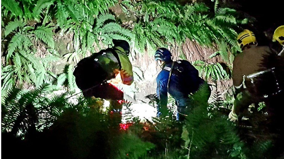 Coastguard rescue woman from ravine with ropes