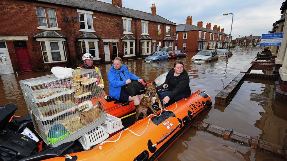 Sophie Thornton and Chris Fairclough with their dog, two cats and a chinchilla are rescued from their flooded home