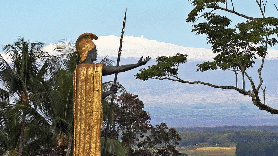 This Jan. 31, 2014, file photo, shows a statue of Hawaiian King Kamehameha I with snow-capped Mauna Kea in the distance, in Hilo, Hawaii.