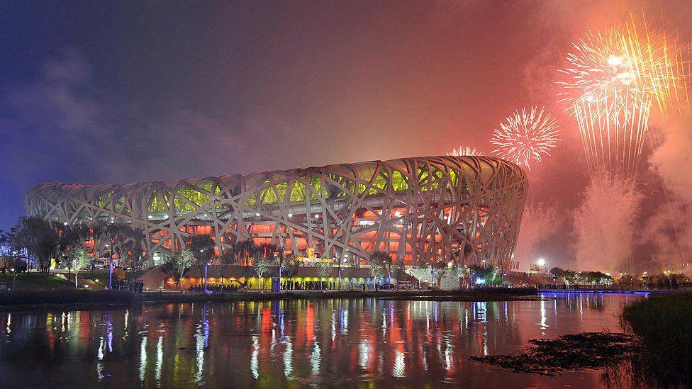 """Los fuegos artificiales explotan sobre el Estadio Nacional, también conocido como el """"Nido de pájaro"""","""