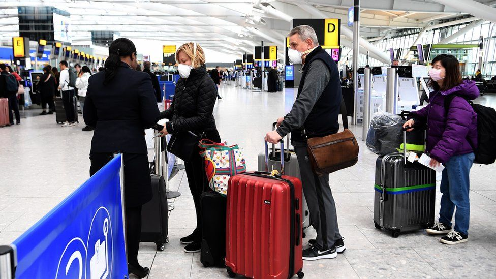 Travellers queue up at Heathrow Airport