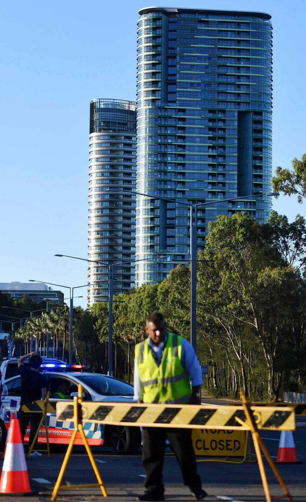 Authorities cordon off a street leading to the Opal Tower (C, back) at Sydney Olympic Park in Sydney, Australia,