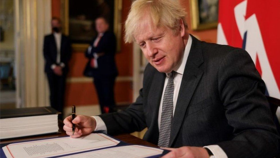Boris Johnson signing the trade deal