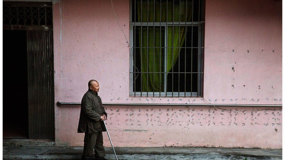Elderly blind Chinese man walks past a building
