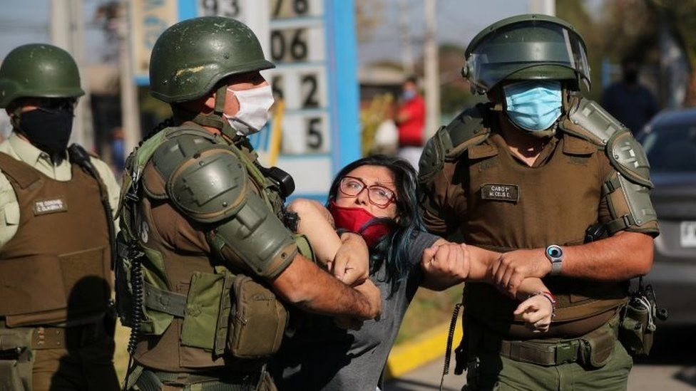 A woman is detained after shouting slogans against riot police at a poor neighbourhood where people are protesting about the lack of help from the government,