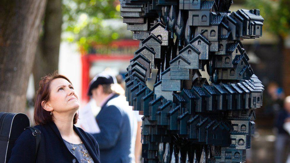 Woman looking at Matthew Plummer Fernandez's Token Homes sculpture