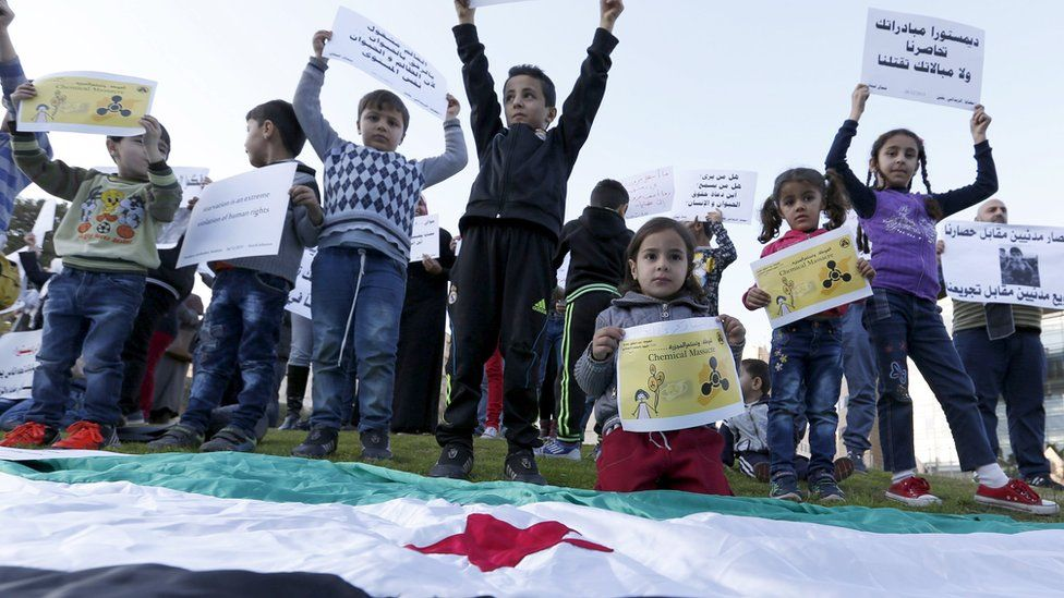 Syrian children carry placards as they call for the lifting of the siege off Madaya and Zabadani towns in Syria, in front of the offices of the U.N. headquarters in Beirut, Lebanon December 26, 2015.