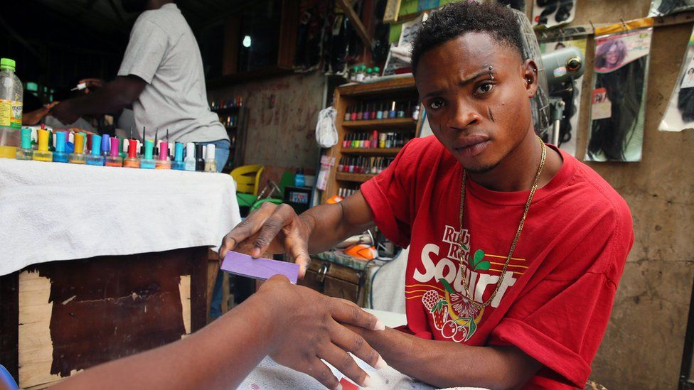 A nail artist fixes client's nail on Valentine's Day at Wuse market in Abuja, Nigeria 14 February 2018