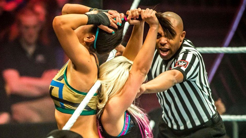 Two women WWE wrestlers fighting in the ring