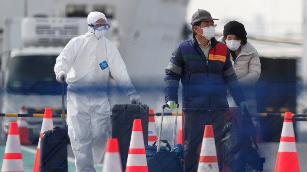 Workers in protective gear escort disembarking passengers to a vehicle from the Diamond Princess cruise ship