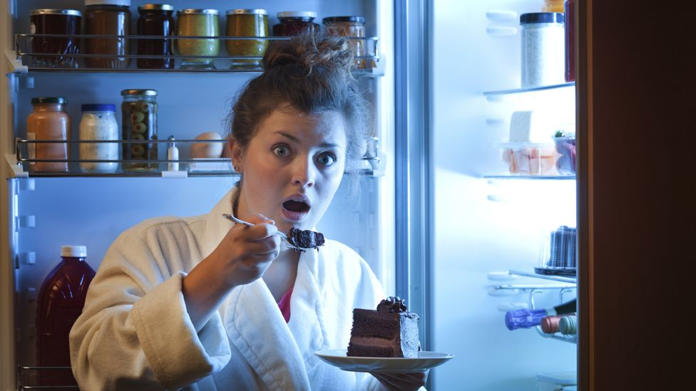 Woman in dressing gown tucking into chocolate cake in front of fridge