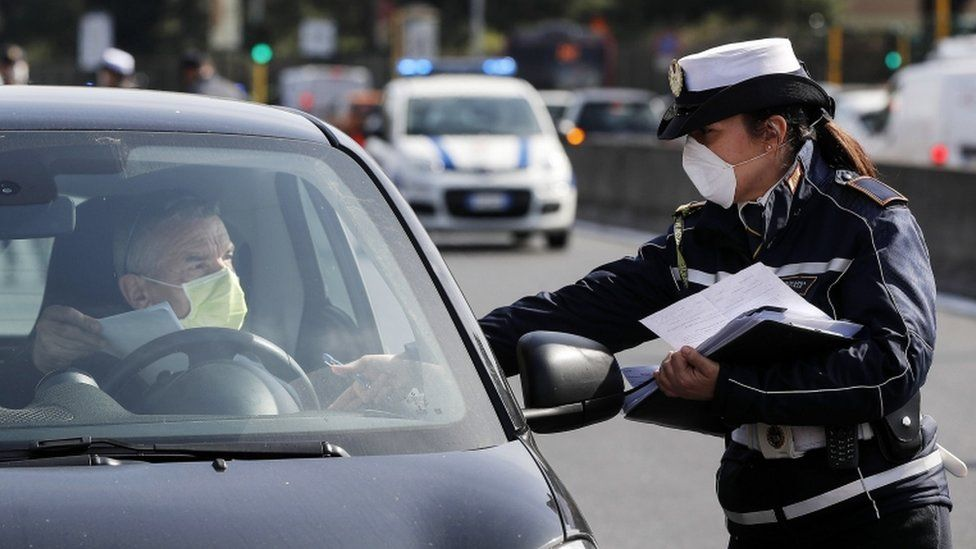 Police officer checking documents of a driver in a car
