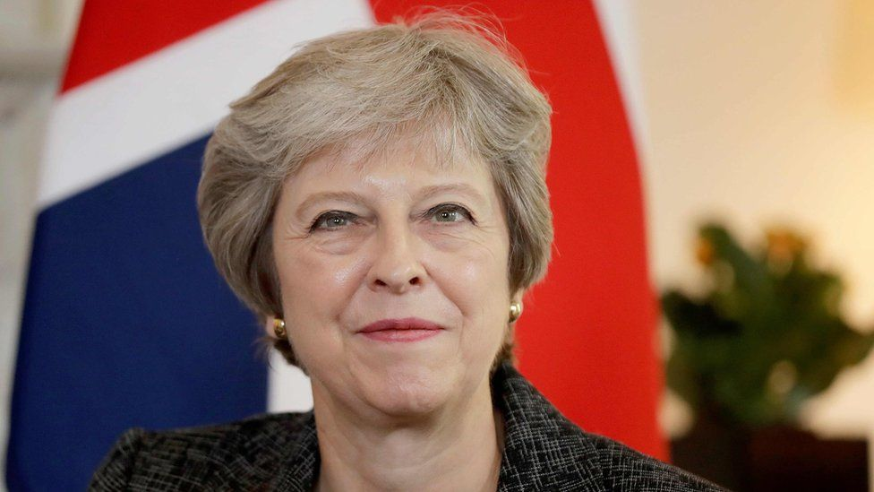 Theresa May in front of a union flag