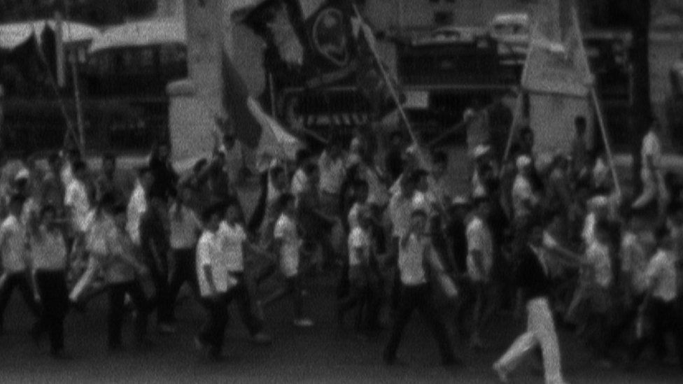 Black and white footage of a political march from the time.