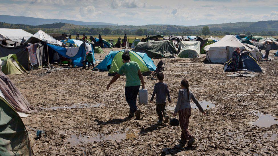 Migrants walk through mud at the migrant camp in Idomeni, Greece, Sunday 22 May 2016.