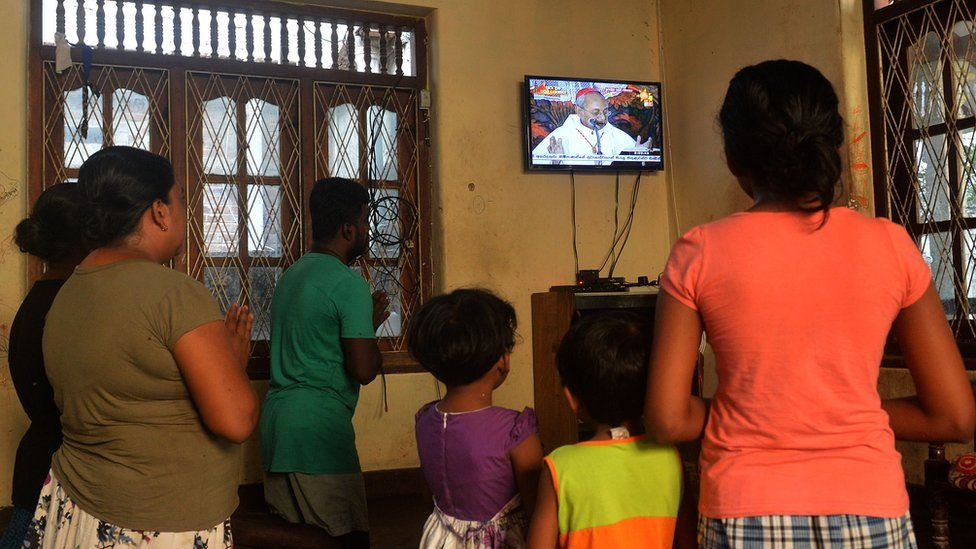 Family in Negombo praying and watching Archbishop of Colombo's service on TV