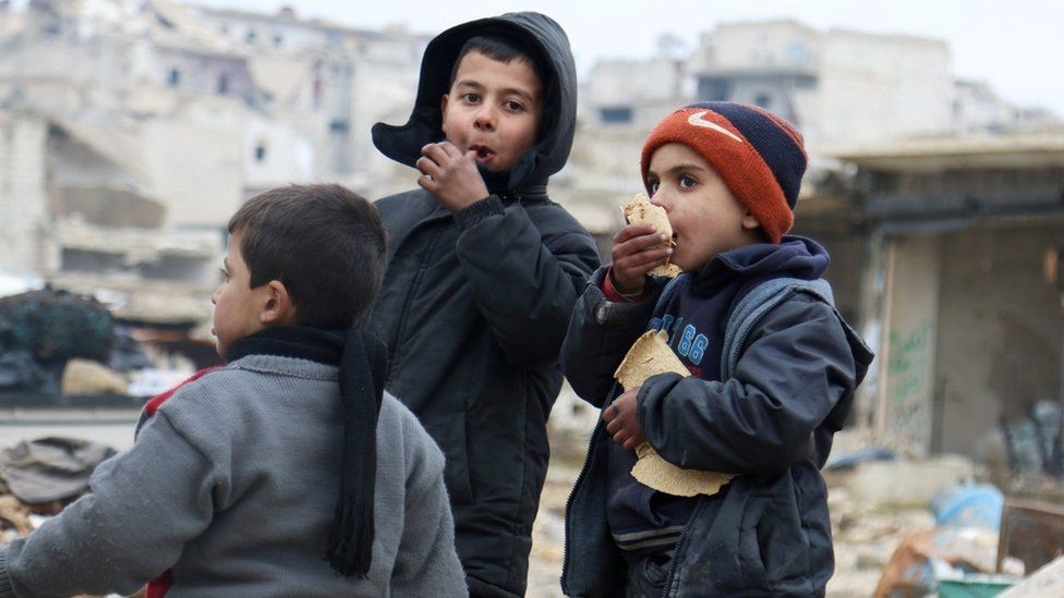 Boys eat bread as they wait to be evacuated from a rebel-held sector of eastern Aleppo, Syria