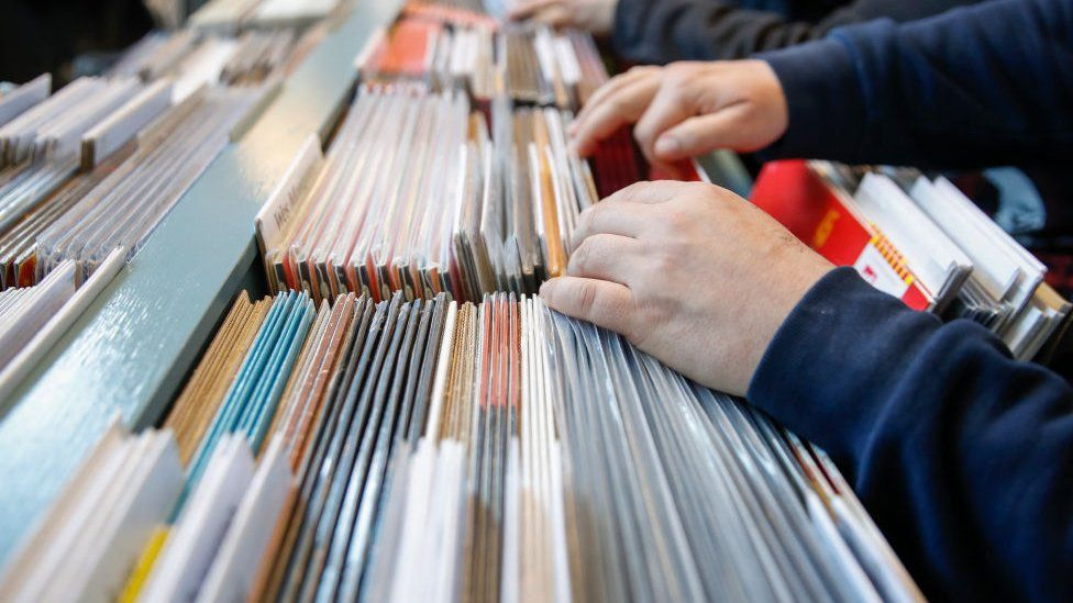 A person looks through vinyl records in a shop