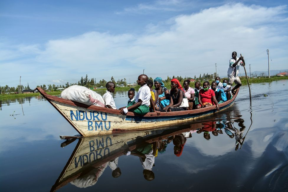 Parents and students ride on a boat to their school in a flooded water area caused by the overflow of Lake Victoria in Kisumu, Kenya on 4 January 2021