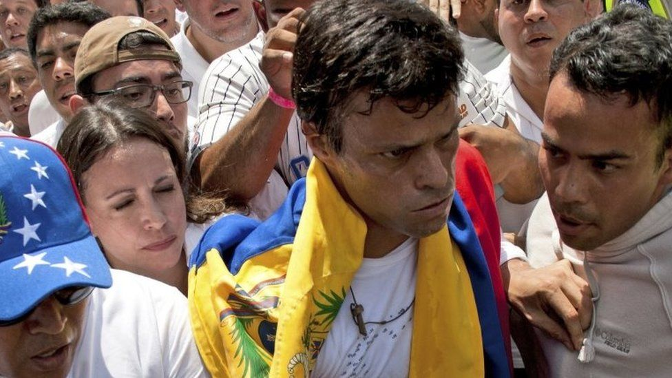 In this file photo from 18 February, 2014, opposition leader Leopoldo Lopez (second from right) draped in a Venezuelan national flag is about to hand himself in to national guards, in Caracas, Venezuela