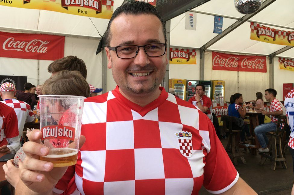 A picture of Croatia fan Daniel holding a pint of beer and smiling