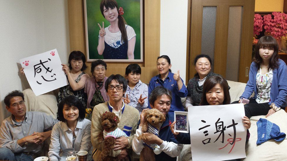 """Top row from left: Narita's wife Hiromi, her mother, her friend, the Tanno sisters (bereaved families), Tamura daughters (bereaved families) Below from left: Takamatsu, journalist, Narita, Mr & Mrs Tamura (bereaved families) - the signs say """"Thank you"""""""