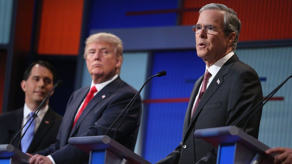 Republican presidential candidates (L-R) Wisconsin Gov. Scott Walker, Donald Trump and Jeb Bush participate in the first prime-time presidential debate hosted by FOX News and Facebook at the Quicken Loans Arena August 6, 2015 in Cleveland, Ohio.