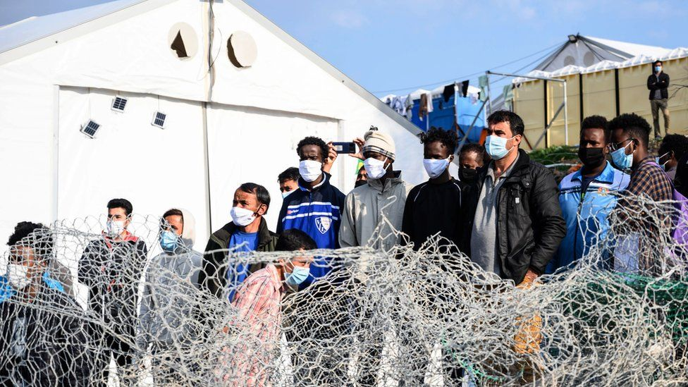 Migrants stand behind a fence at Karatepe refugee camp on Lesbos island, Greece, 29 March 2021