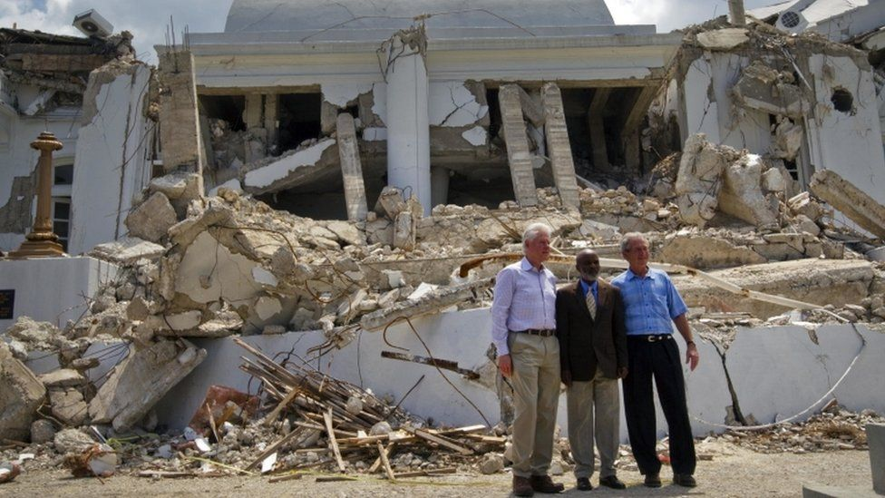 Rene Preval stands next to former US presidents Clinton and Bush outside the presidential palace two months after the 2010 quake, March 22 2010