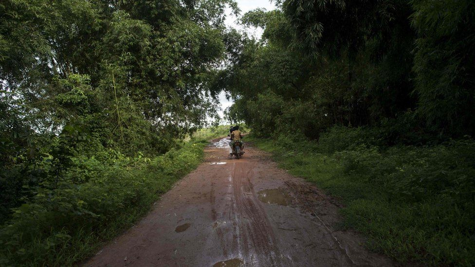 The girls' mother rides on the back of a motorbike down a dirt road. 20 September 2016.
