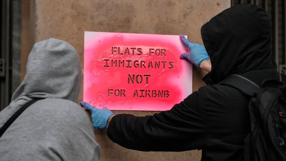 "Activists stencil a slogan reading ""Flats for immigrants not for airbnb"" on a wall during a demonstration in Athens."