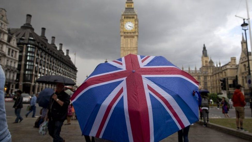 A pedestrian shelters from the rain beneath a Union flag themed umbrella in London. File photo