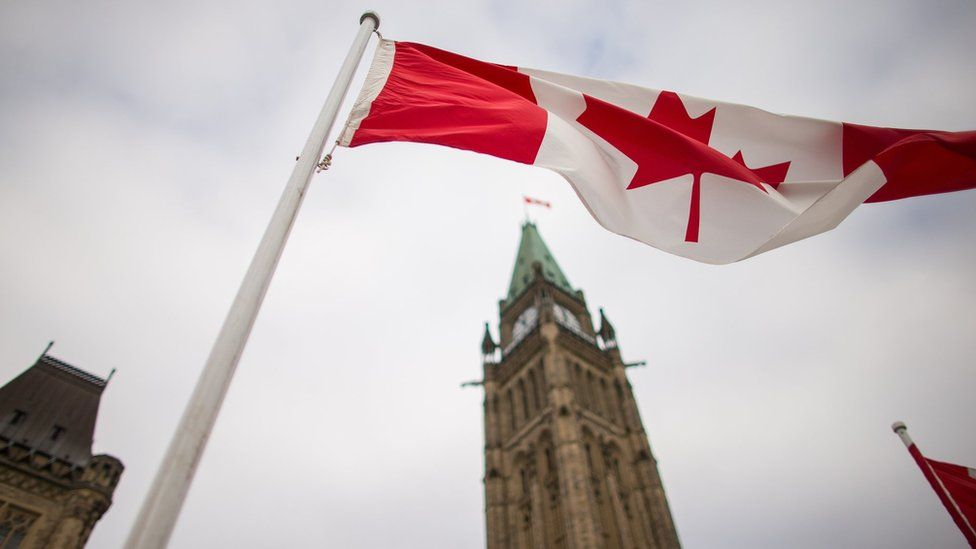 A Canadian flag flies in front of the peace tower on Parliament Hill in Ottawa, Canada on December 4, 2015