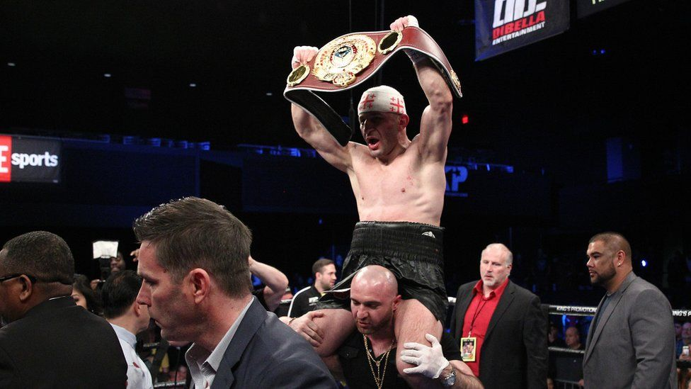 Khurtsidze on shoulders with a belt above head