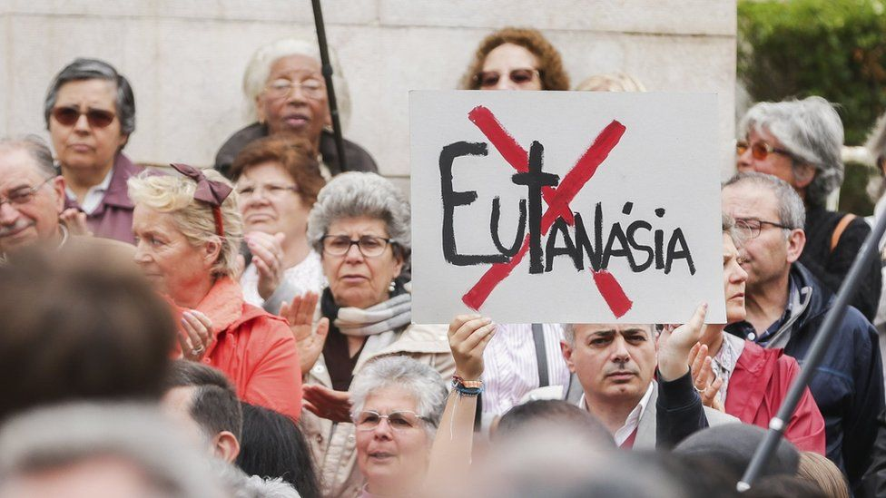 A man holds a sign with a cross struck through the word euthanasia at a demonstration against euthanasia in front of the Portuguese Parliament in Lisbon, Portugal, 29 May 2018