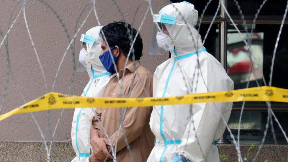 Police officers wearing protective suits a man from an apartment under enhanced lockdown in Kuala Lumpur (1 May 2020)