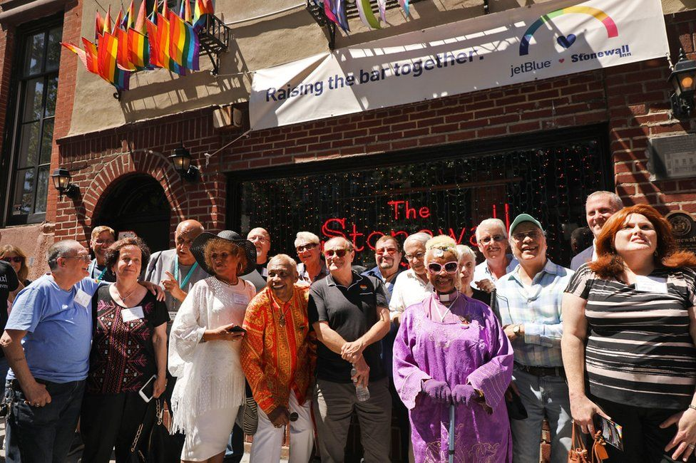 Some of the people who were at the Stonewall Inn the night the historic gay bar was raided by police in 1969 gather for a photo in front of the bar