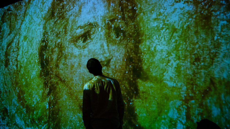 A visitor to Tate Britain standing in front of a William Blake projection