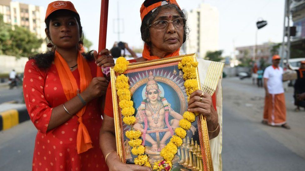 A woman holding a framed poster of a Hindu god followed by another woman
