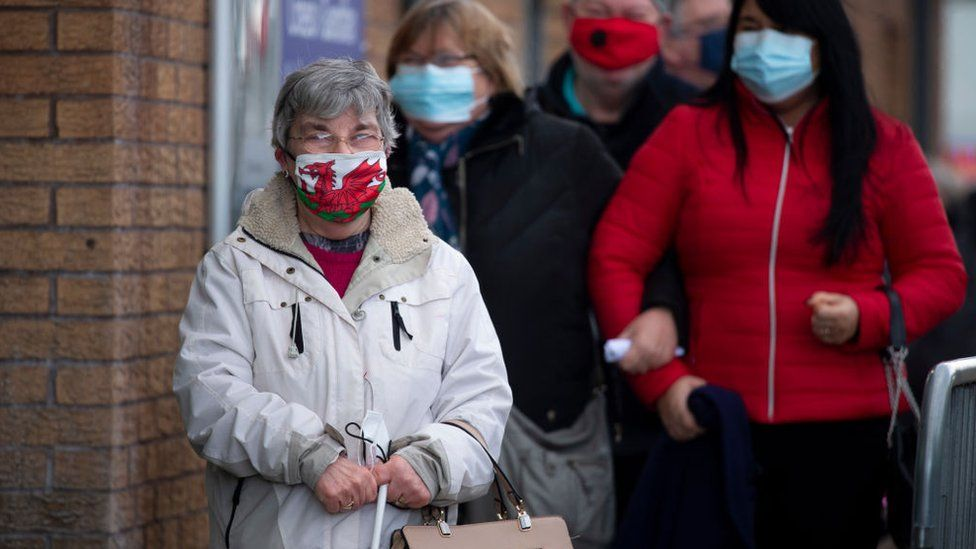 A woman wearing a Welsh flag face mask stands in a queue for vaccine