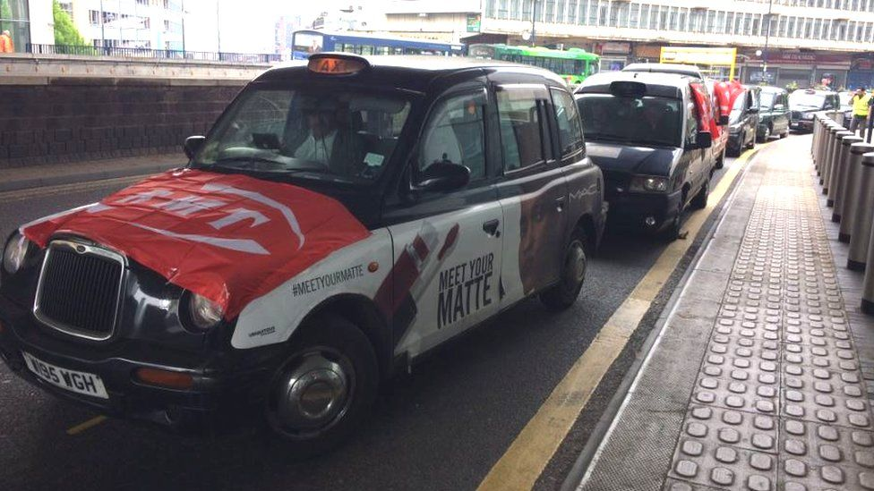 Taxis in Birmingham displaying RMT flags and posters