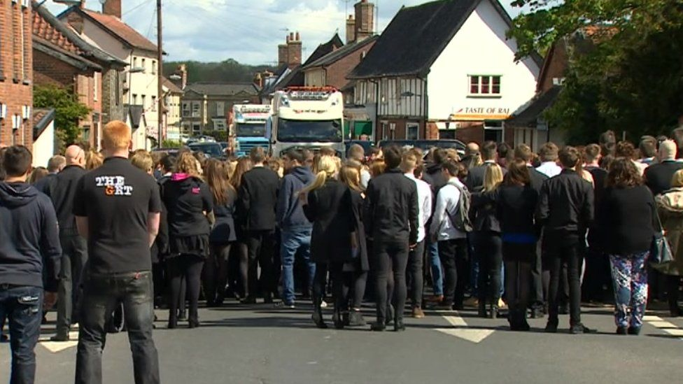 Crowds gathered in front of lorry convoy