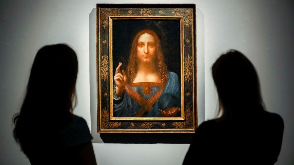 Staff members pose next to a painting by Leonardo da Vinci entitled Salvator Mundi before it is auctioned at Christie's in New York